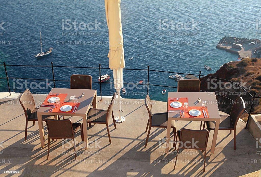 Alfresco cafe on terrace over sea coast, Santorini, Greece stock photo
