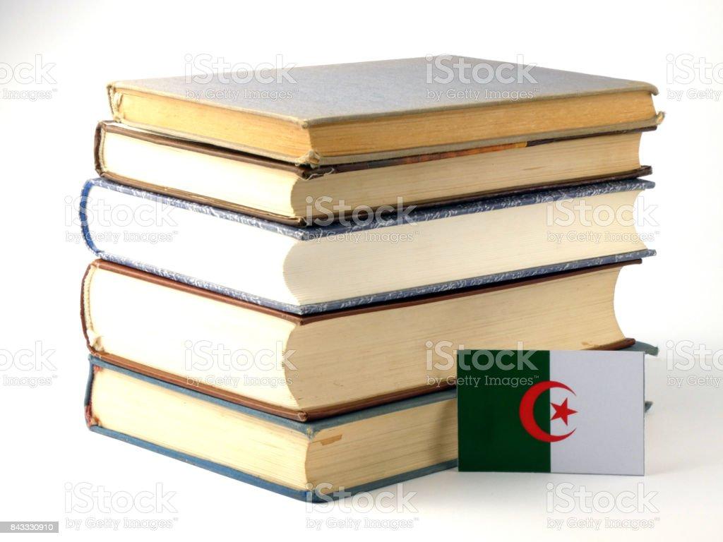 Algerian flag with pile of books isolated on white background stock photo