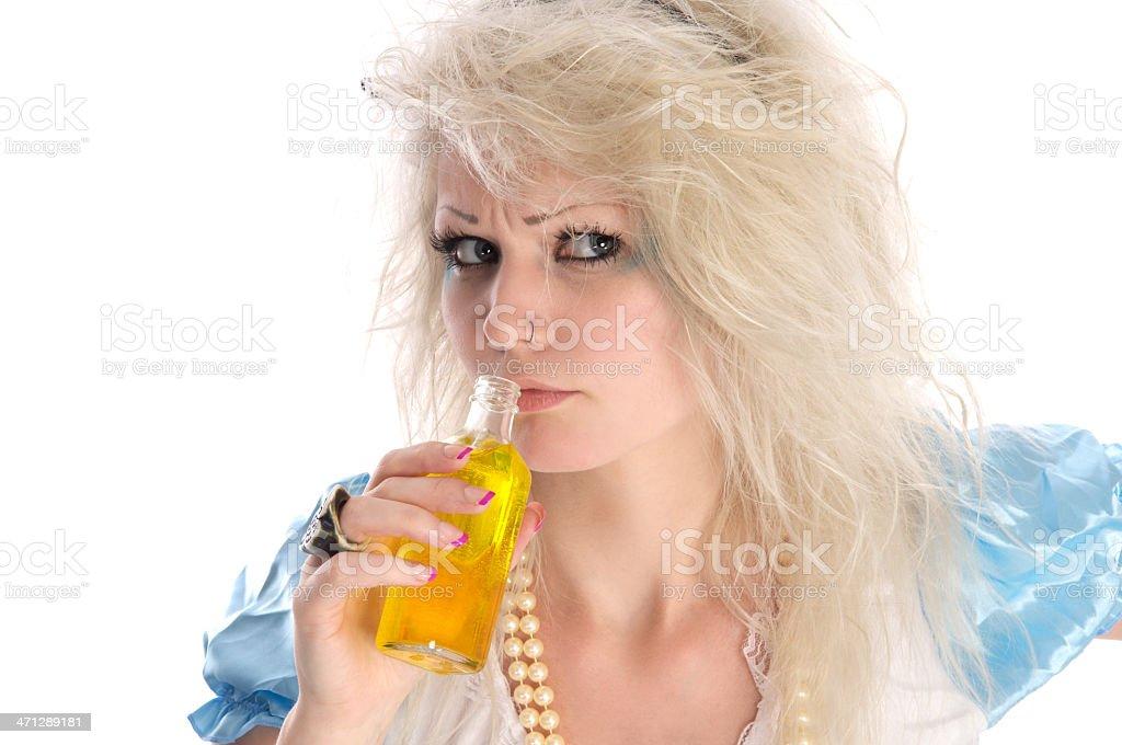Alice looks suspicious smelling potion. stock photo
