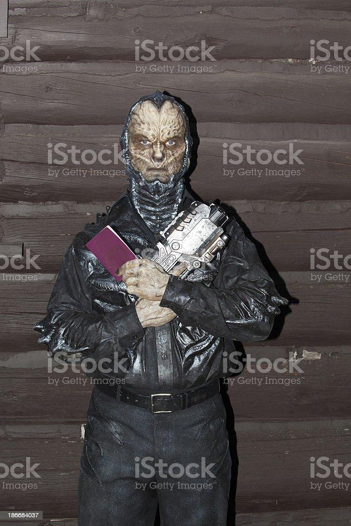 alien holds British passport and futuristic gun royalty-free stock photo