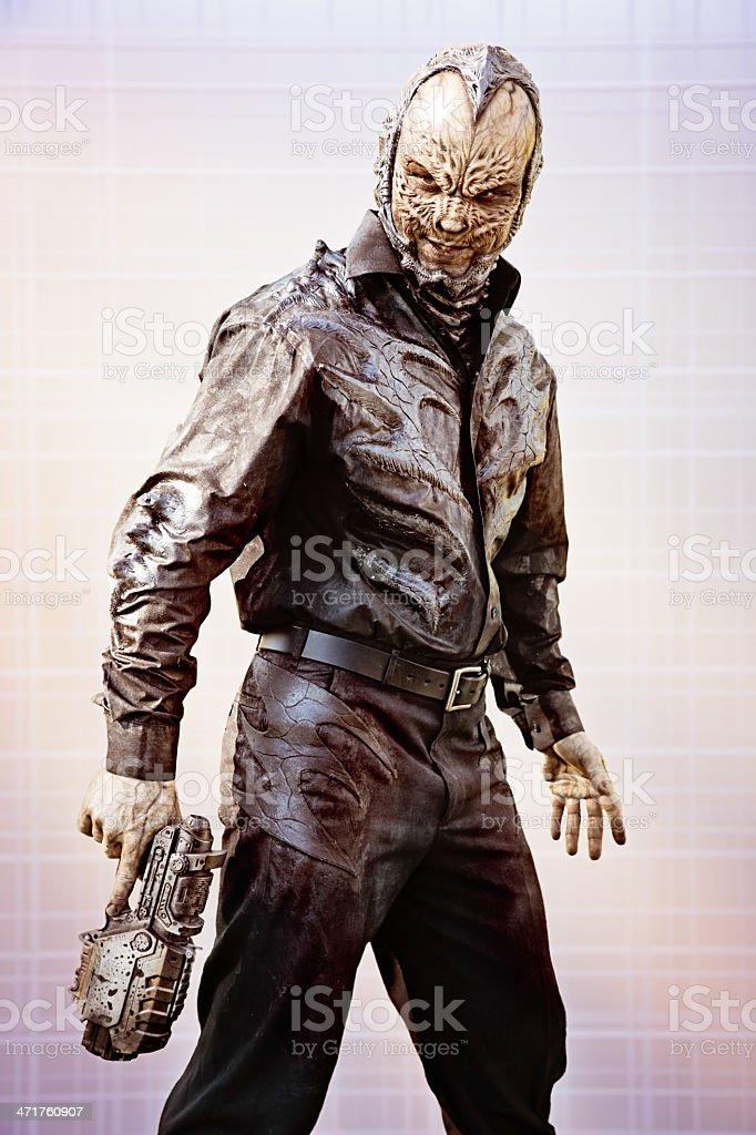 Alien humanoid with futuristic gun stock photo