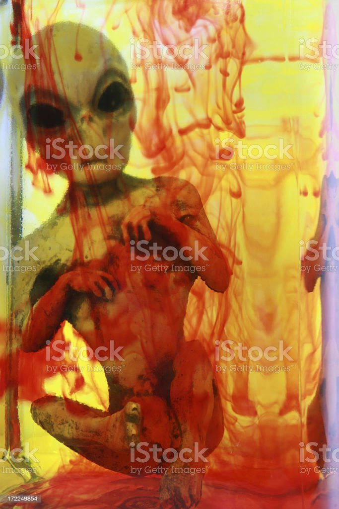 Alien in a solution of yellow and red liquid stock photo
