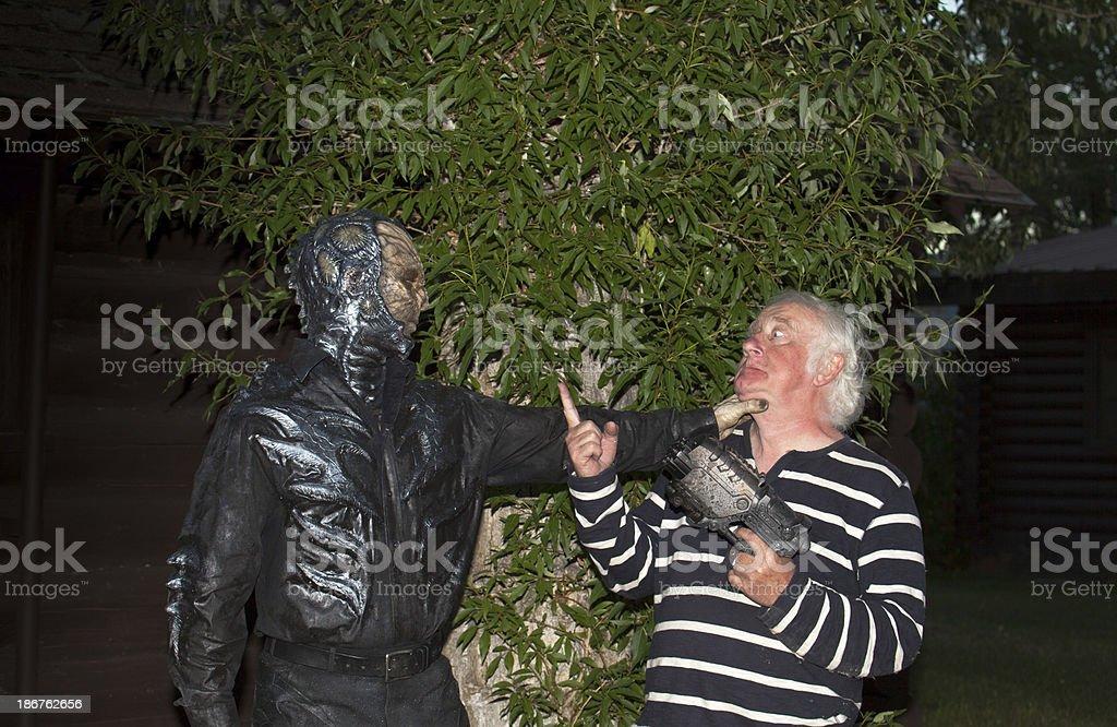 alien strangles senior holding futuristic gun royalty-free stock photo