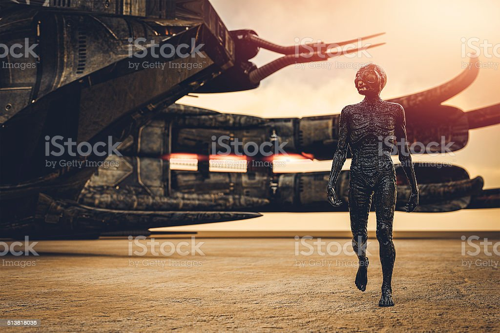 Alien with spaceship, walking in desert stock photo