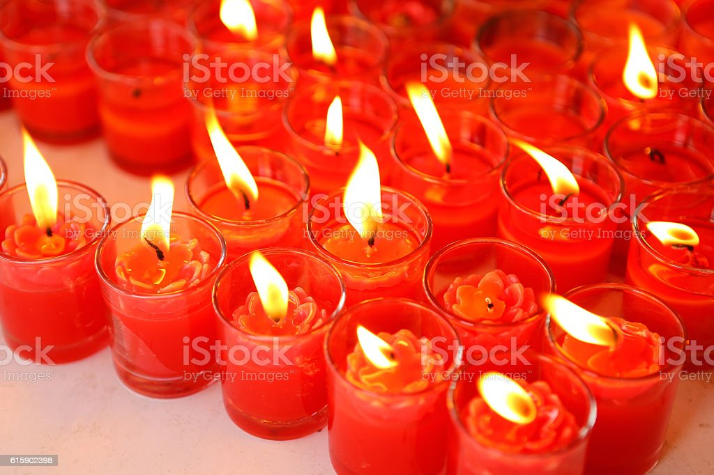aligned Red candles burning in glass stock photo