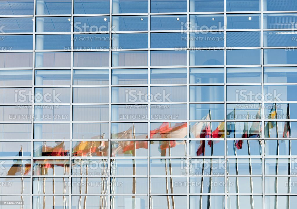 All European Union flags reflected in European Parliament facade stock photo