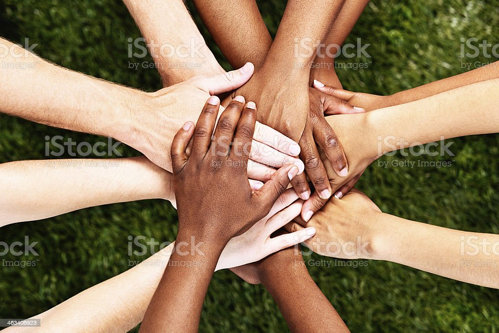 All for one! Hands stacked in unity and support stock photo