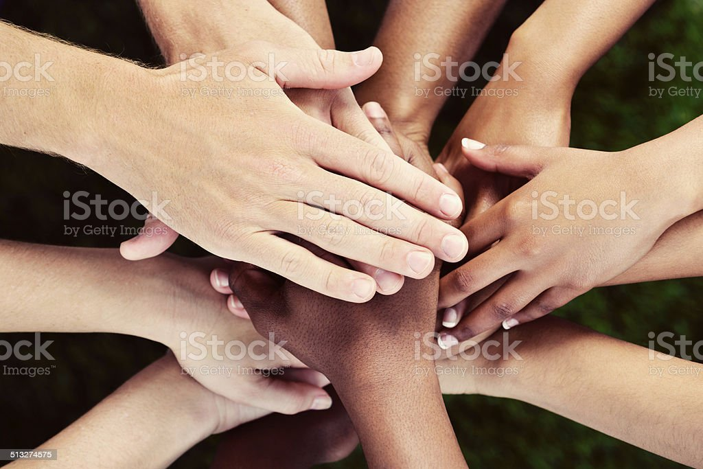 All for one! Many hands stacked in mutual support. stock photo