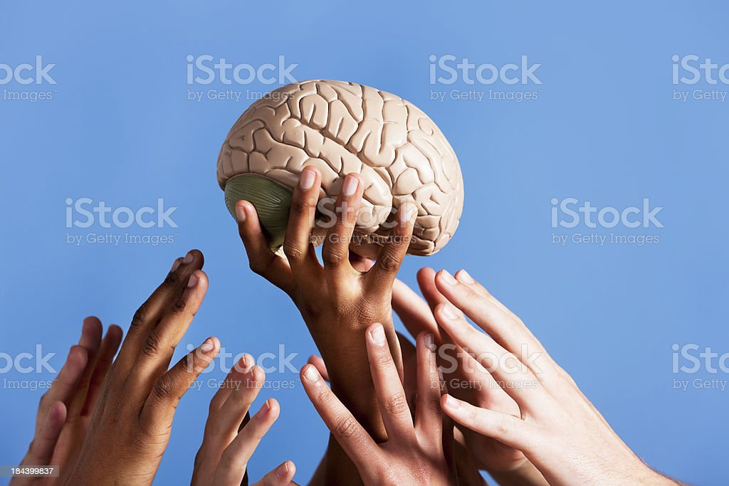 All ready for some blue-sky thinking, hands reach towards brain stock photo