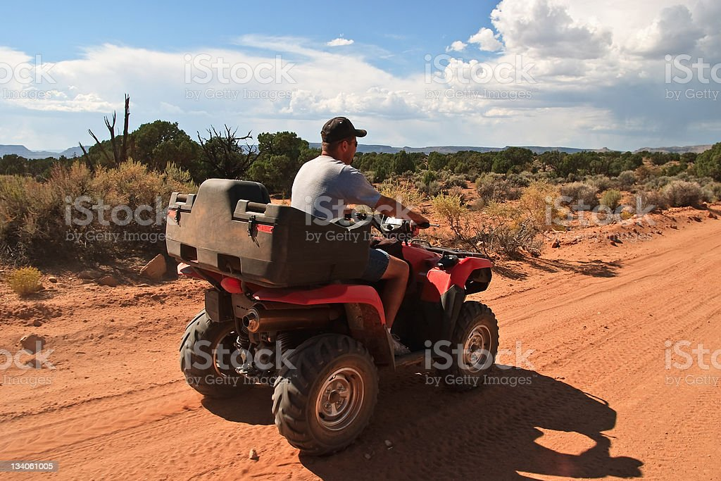 Man riding his ATV in the high plateau desert country of southern...