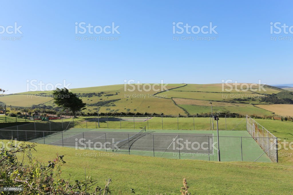 all weather surface tennis court aomngst grass and hills stock photo