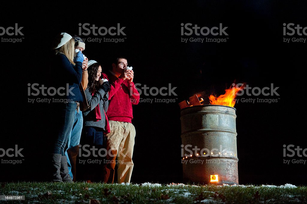All-American Friends Sip Hot Cocoa by Campfire royalty-free stock photo