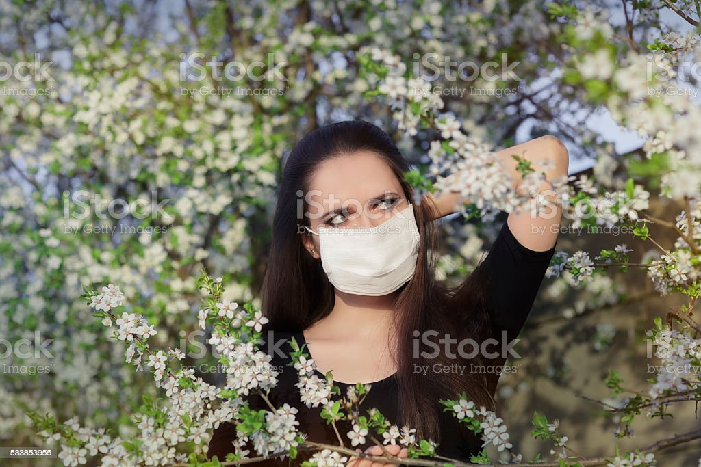 Allergic Girl with Respirator Mask in Spring Blooming Decor stock photo