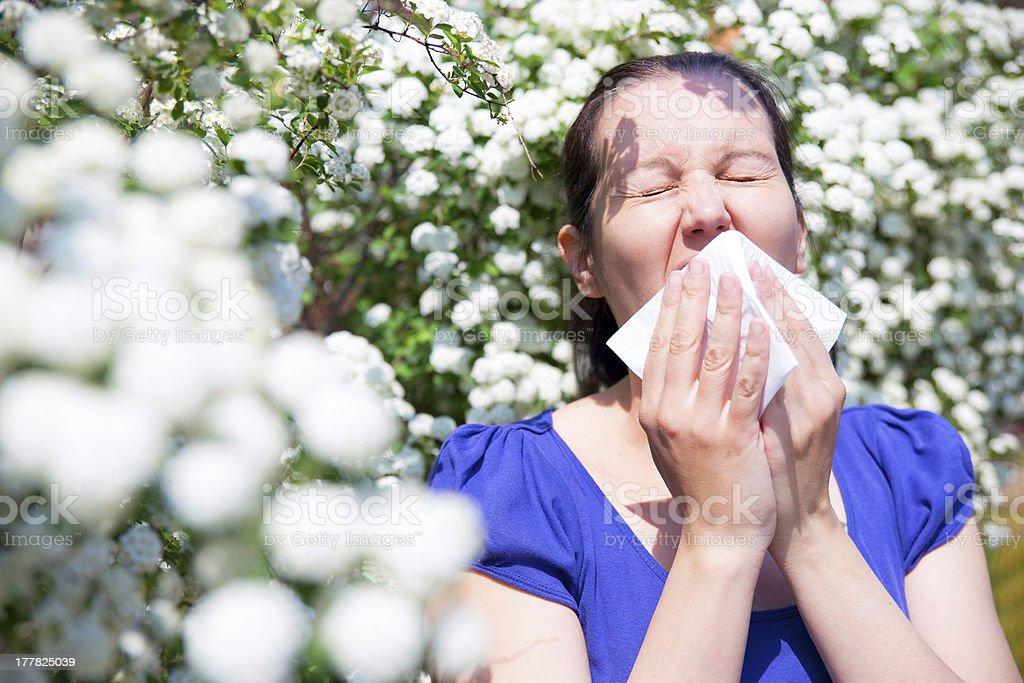 Allergic woman sneezing in handkerchief stock photo
