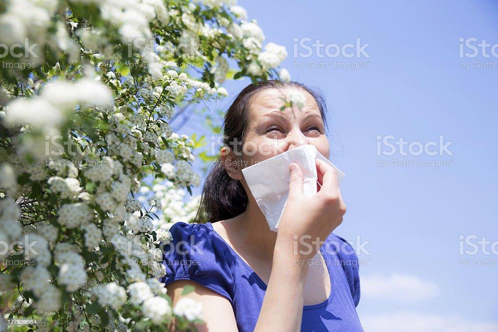 Allergic woman sneezing in handkerchief royalty-free stock photo