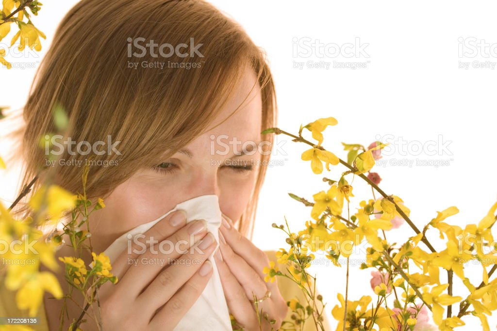 A young woman sneezing among flowers.Other similar images: