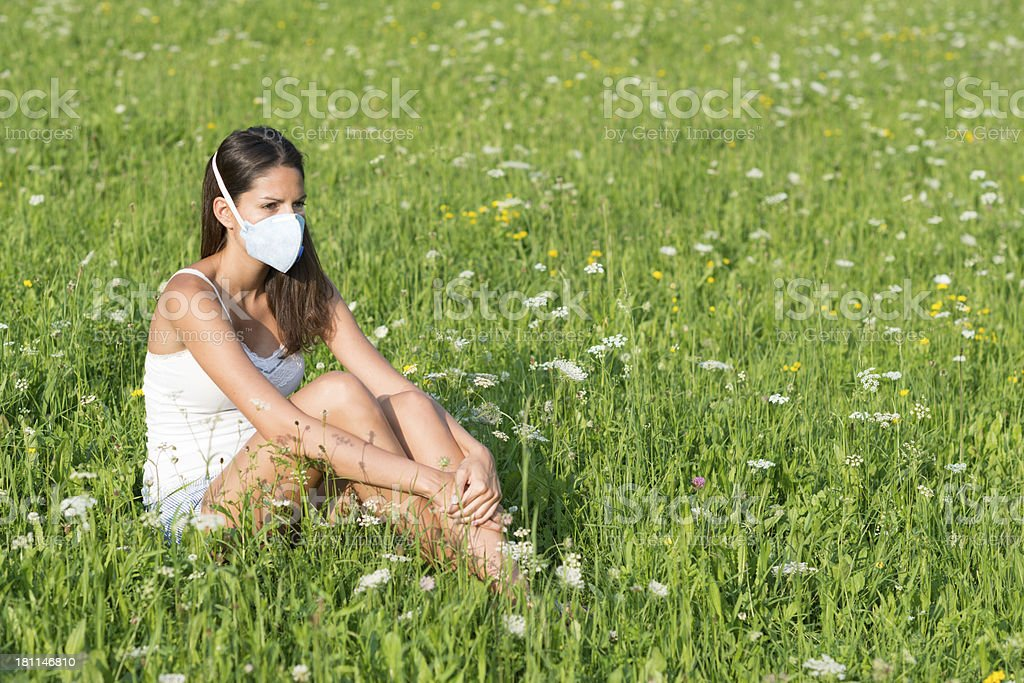 Beautiful woman wearing a anti-allergy respirator face mask to filter...