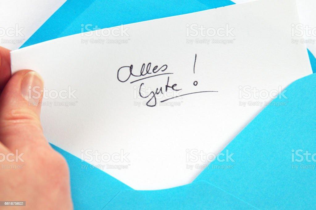 Alles Gute (All the best), hand holding handwritten letter in blue envelope stock photo