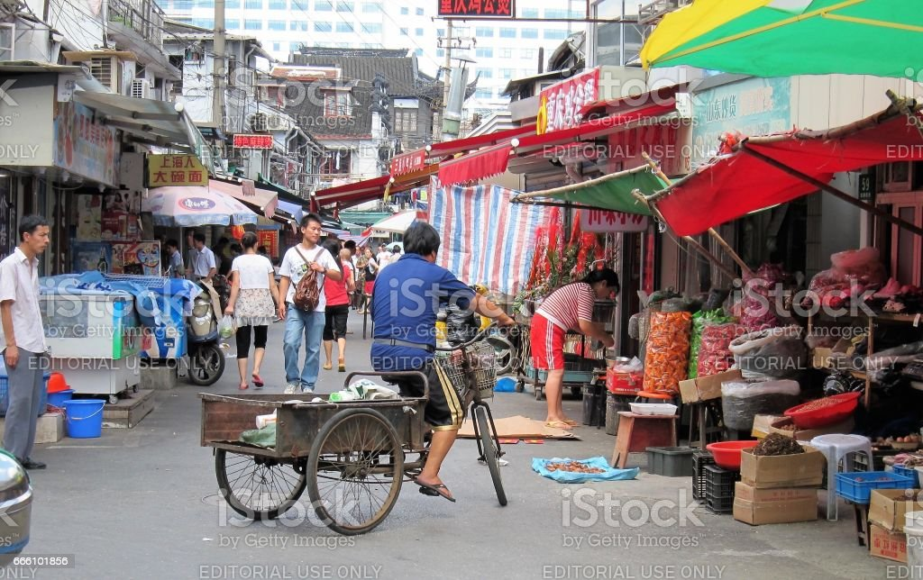 Alley way of Shanghai low rise old residential area. Markets and tricycles are common sight. stock photo