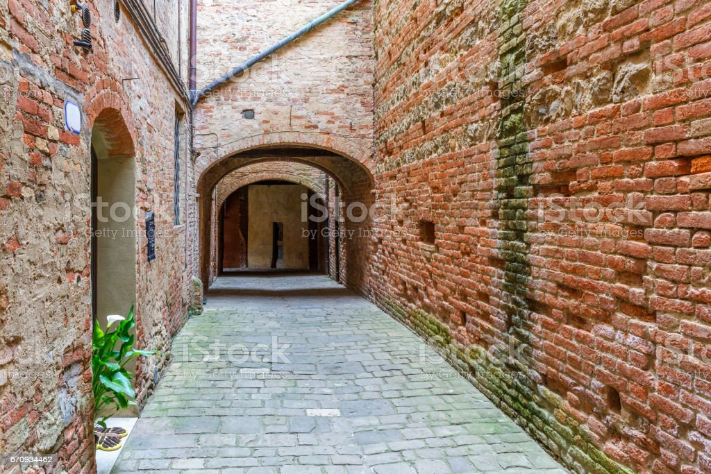 Alley with brick walls in an Italian village stock photo