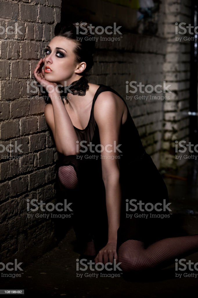 Alley with Brunette Young Woman Fashion Model in Black Dress stock photo