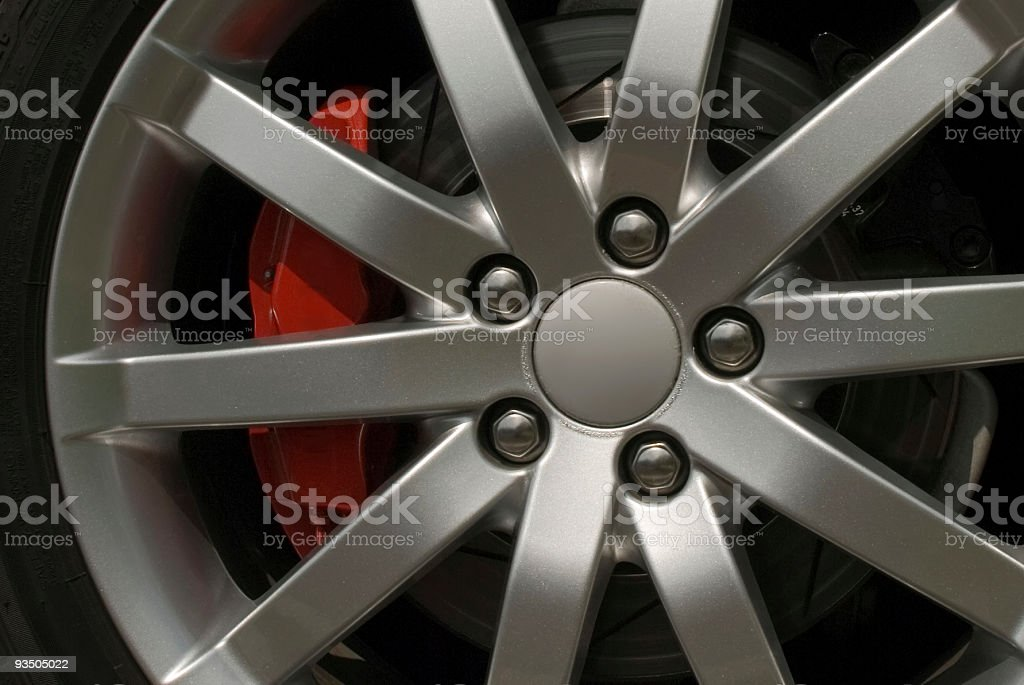 Alloy wheel with red brake calliper and five nuts stock photo