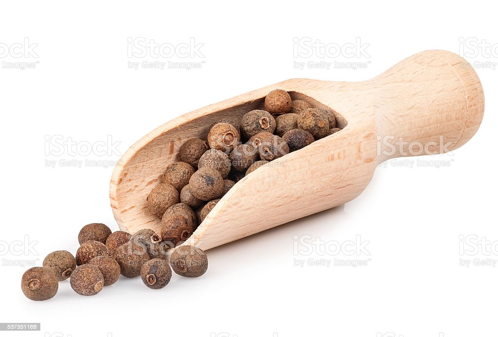 allspice in wooden scoop isolated on white background stock photo