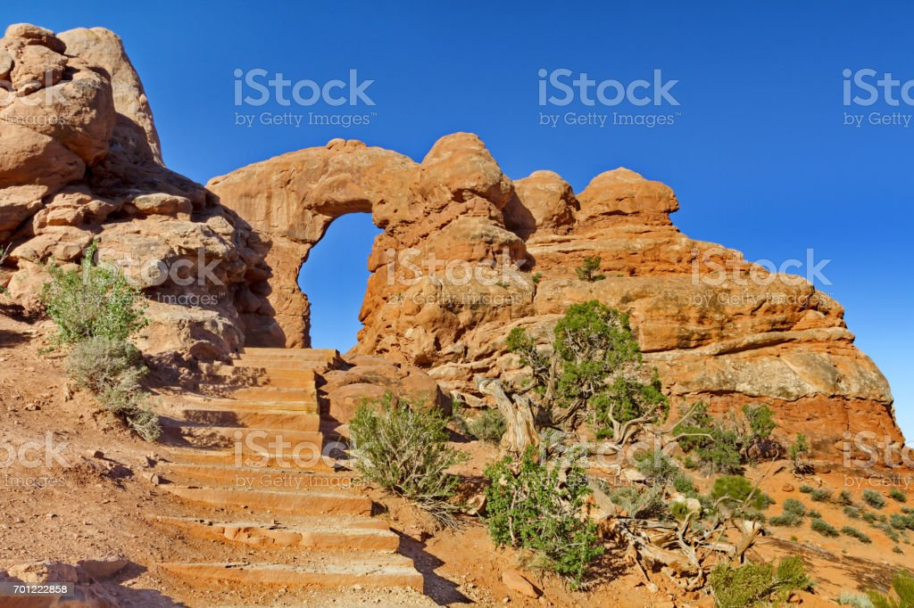 Allure of steps leading up to Turret Arch framed against blue sky stock photo