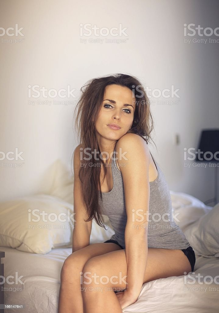 Alluring Woman Sitting on Top of Your Bed stock photo