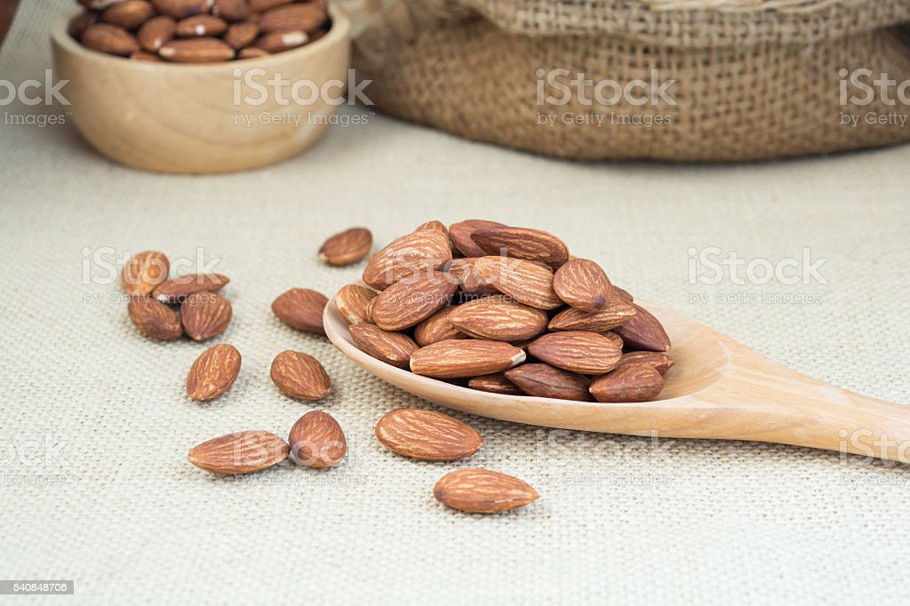 Almond in wood spoon stock photo