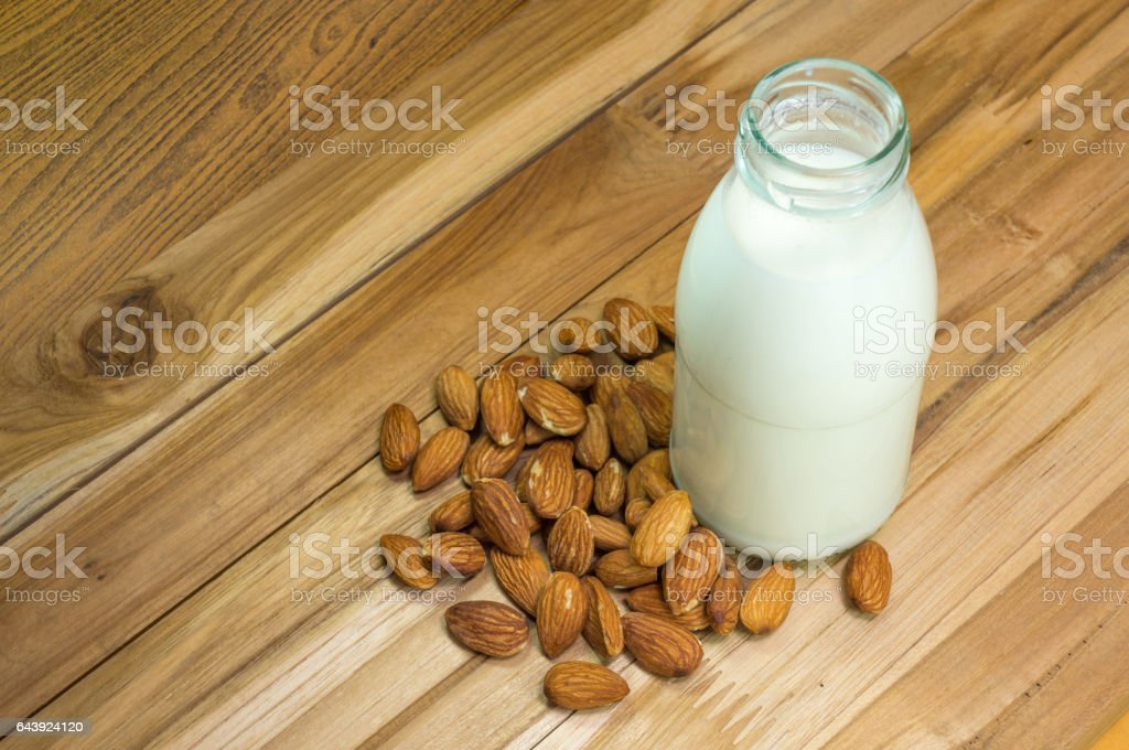 Almond milk in bottle glass with almonds on wooden. stock photo