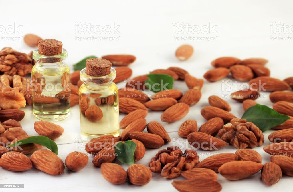 Almond nuts and oil in bottles stock photo