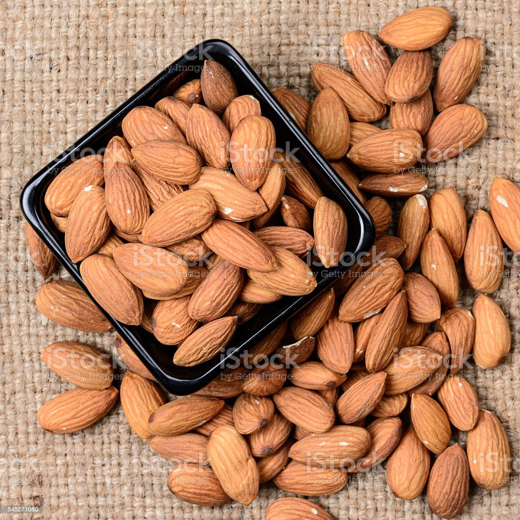 almonds - a ceramic bowl on grained background stock photo