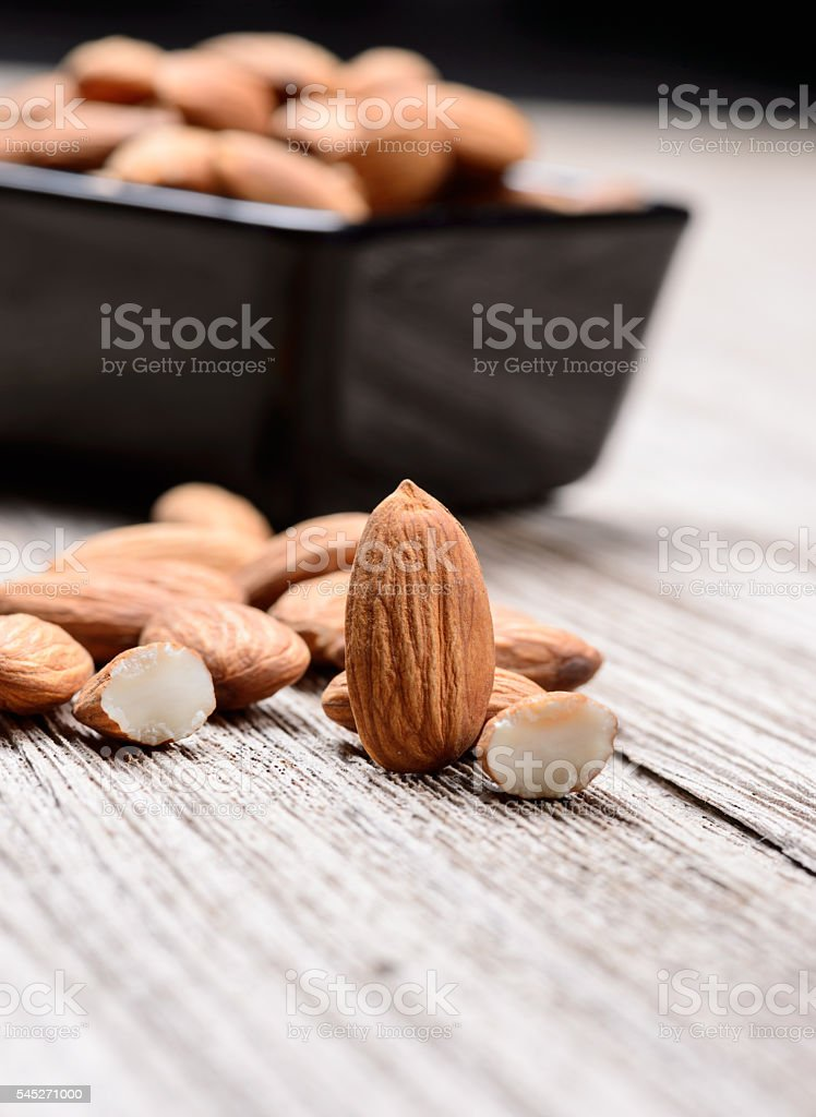 almonds - a ceramic bowl on grained wood background stock photo