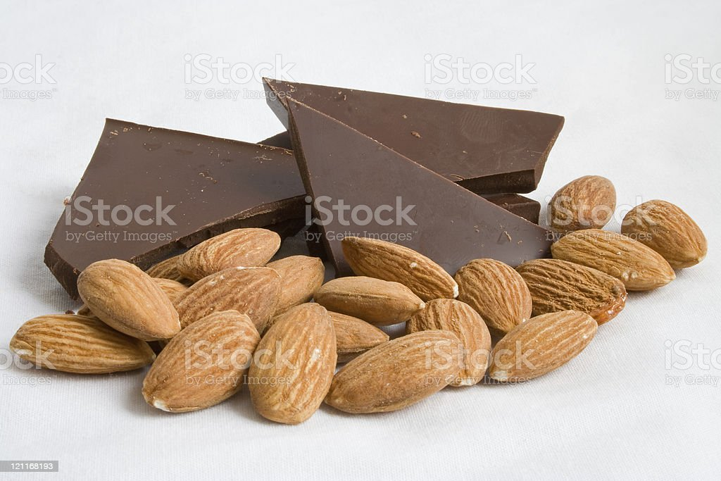 Almonds and dark chocolate pieces isolated on white stock photo