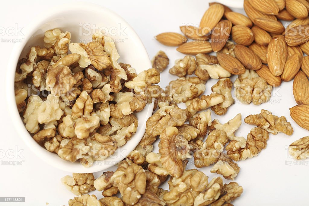 Almonds and walnuts spilled out of white bowl royalty-free stock photo