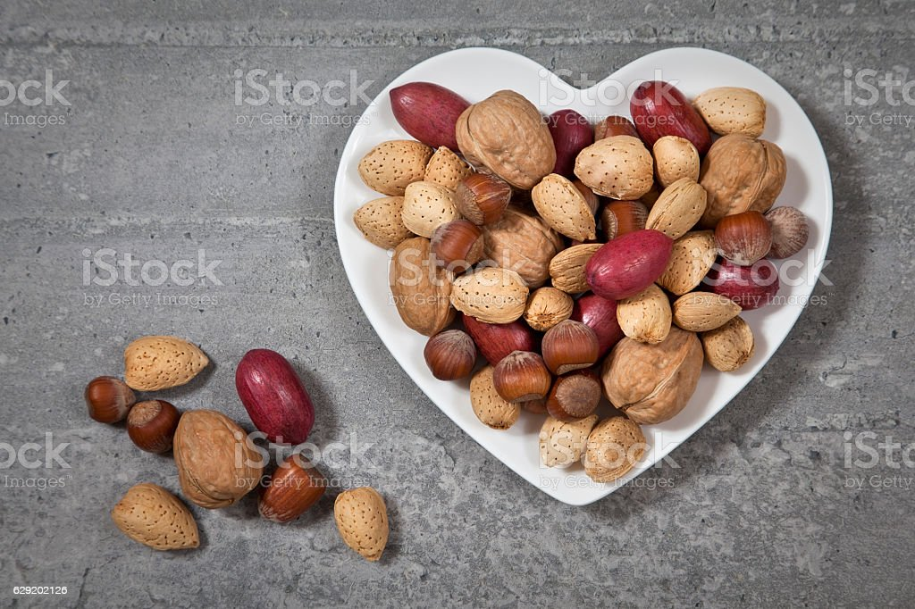Almonds in a white heart shape plate stock photo
