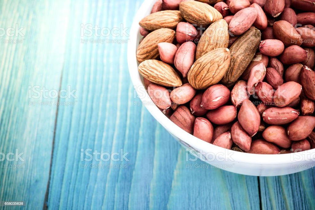 Almonds in blue  bowl on wooden background stock photo