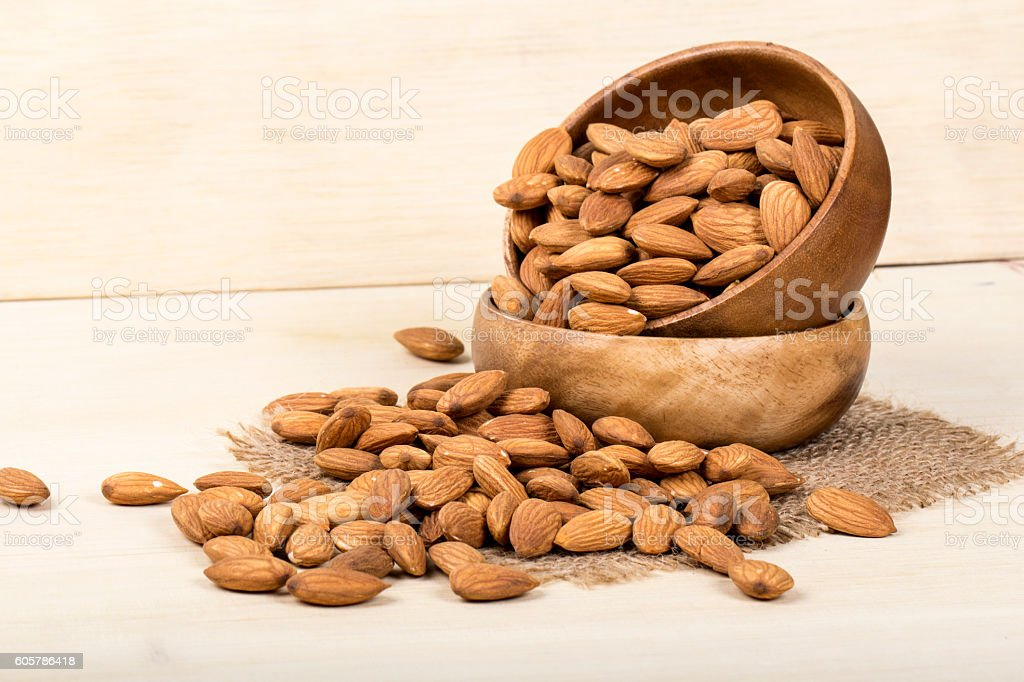 Almonds in brown bowl on wooden background, group of almonds stock photo