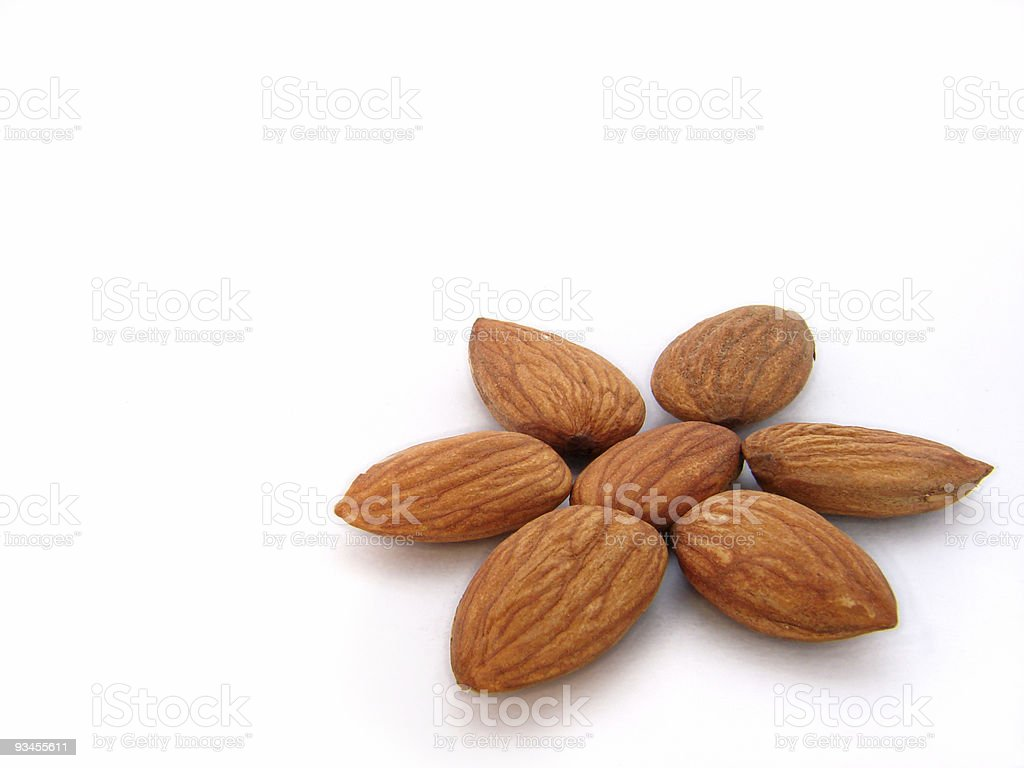 Almonds in flower pattern on white background royalty-free stock photo