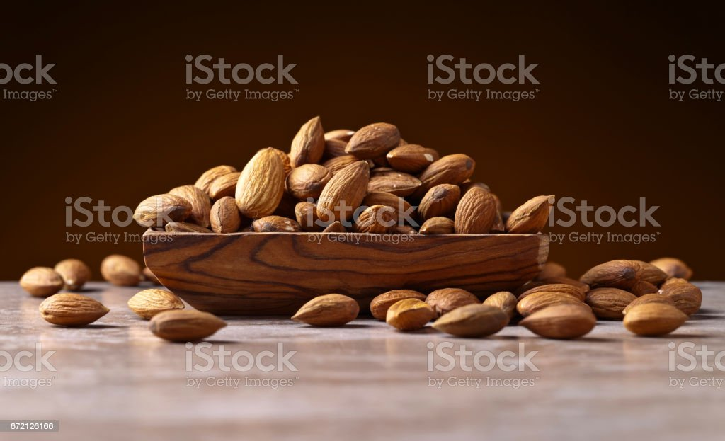 Almonds in old wooden dish stock photo