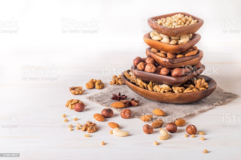 almonds, walnuts, hazelnuts cashews and pine nuts in wooden bowl stock photo