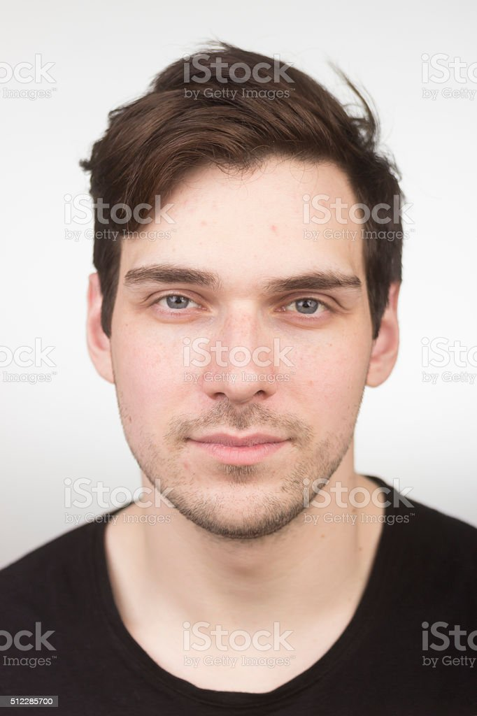 Almost blank expression, face close up young man. stock photo