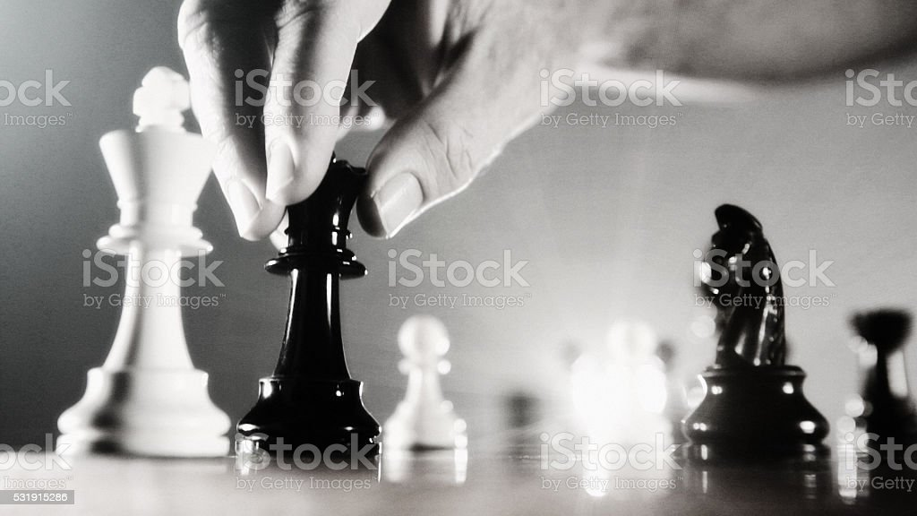 Almost checkmate: male hand with black queen approaching white king stock photo