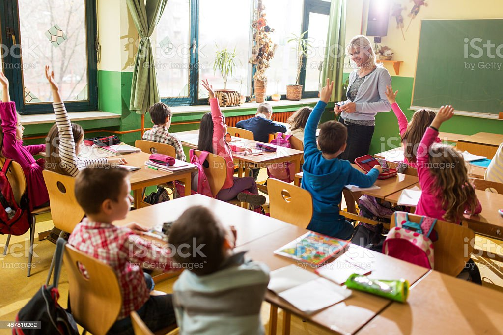 Almost everyone knows the answer to teacher's question. stock photo