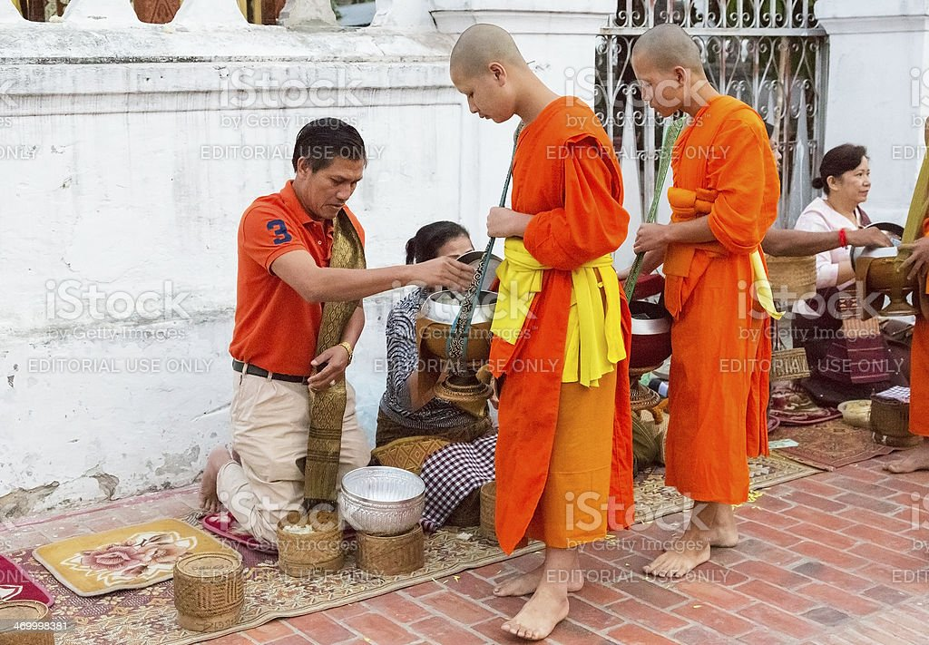 Alms giving early morning in Luang Prabang, Laos. stock photo
