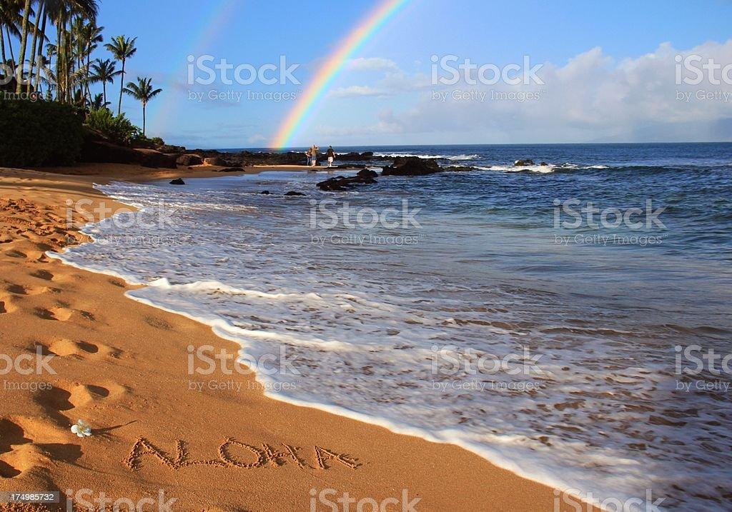 Aloha written on Maui Hawaii beach sand with double rainbow stock photo