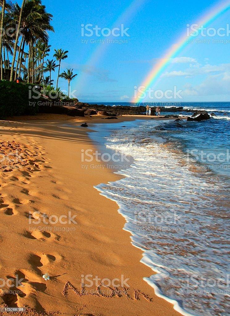 Aloha written on Maui Hawaii beach sand with double rainbow royalty-free stock photo
