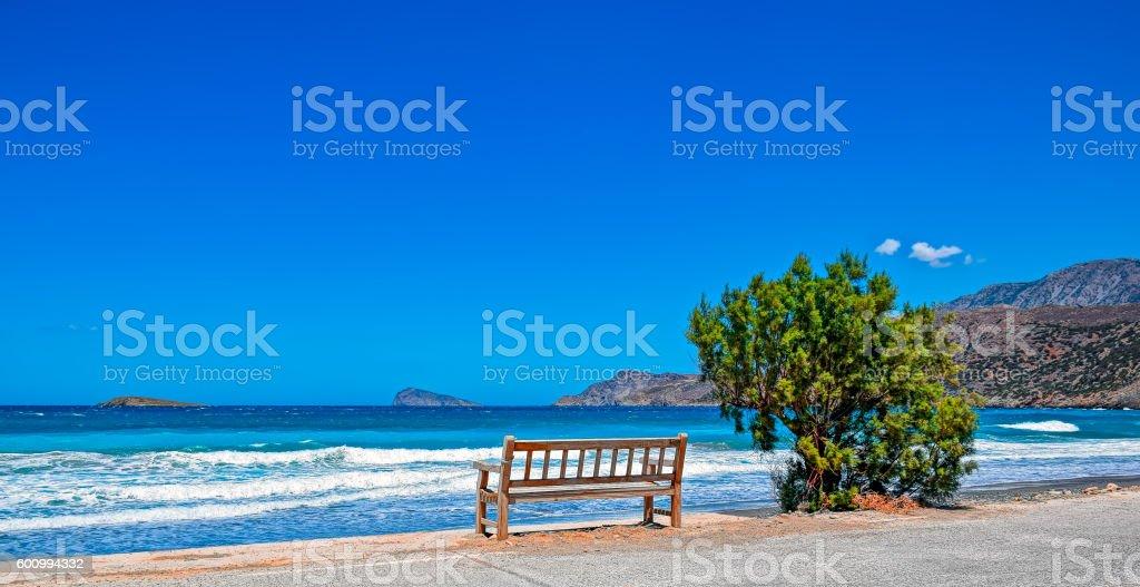 Alone bench on sea shore stock photo