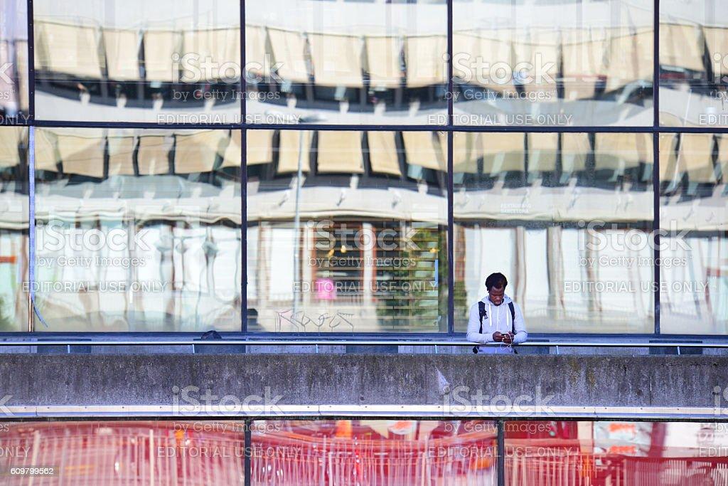 Alone black man, using phone, Sergels Torg, Stockholm stock photo